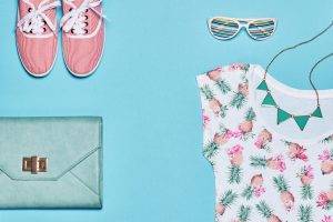 Summer Fashion girl clothes set, accessories. Creative hipster pastel colors. Stylish gumshoes, trendy dress, handbag clutch, necklace sunglasses. Unusual modern. Overhead, top view, blue background
